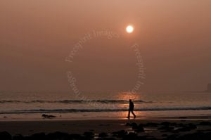 Sunset and lone walker on Llantwit Major Beach  - to add a point of interest