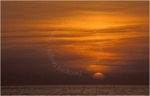 Clarach Bay Sunset Cardigan Bay West Wales with a long lens and the sun positioned roughly on the third